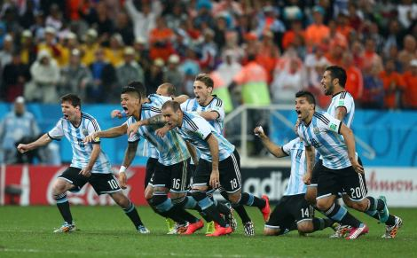 Argentina players celebrate as they win the penalty shoot out and qualify for the final to face Germany